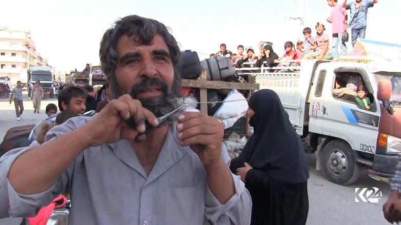 Een inwoner van Manbij knipt zijn baard af, nu IS is vertrokken. Foto: Kurdistan24