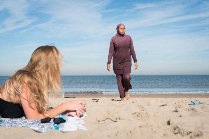 2016-08-25 00:00:00 ILLUSTRATIE - Een meisje in bikini kijkt toe terwijl een vrouw in boerkini de zee verlaat. ANP XTRA ROOS KOOLE **MODEL RELEASED, BEELDEN UITSLUITEND VOOR REDACTIONEEL GEBRUIK**