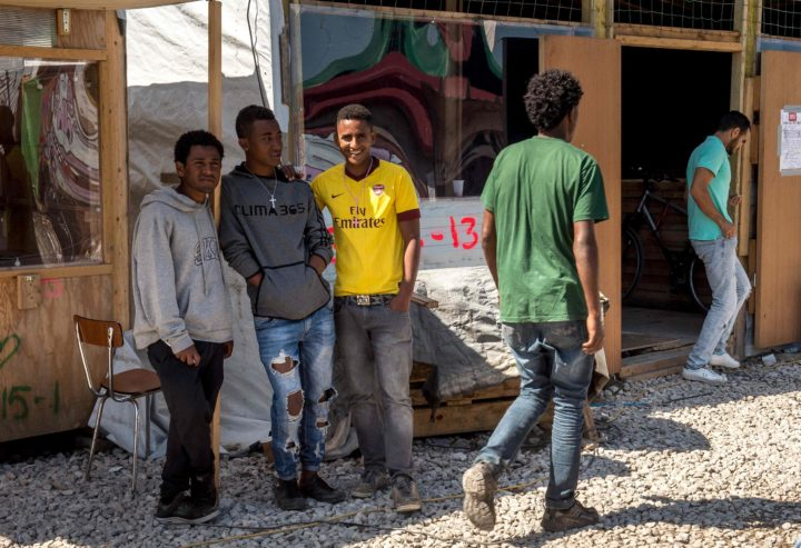 "2016-08-12 12:41:53 Migrants meet and chat in front of a makeshift shop in the so-called 'Jungle' migrant camp in the French northern port city of Calais on August 12, 2016. A French judge on Friday rejected a bid by authorities in Calais to close unlicensed shops and eateries in the migrant camp. The authorities sought an emergency order to close 72 unlicensed stalls and restaurants dotted among the tents housing at least 4,500 migrants and asylum-seekers who are aiming to reach Britain. But in his ruling, the judge said that while the concerns expressed were ""completely understandable,"" the matter was not urgent enough to warrant the expulsion of the vendors. / AFP PHOTO / PHILIPPE HUGUEN"