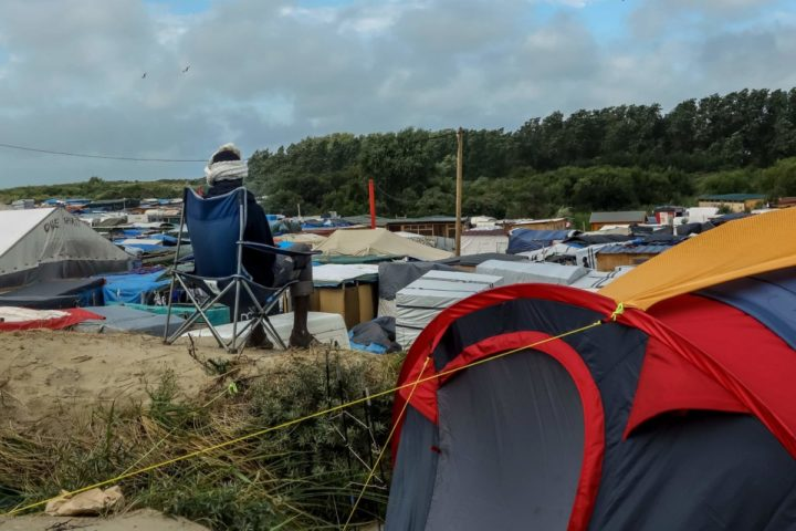 "2016-08-22 11:57:59 A migrant next to his tent, overlooks the so-called ""Jungle"" migrant camp on August 22, 2016 in Calais. / AFP PHOTO / PHILIPPE HUGUEN"