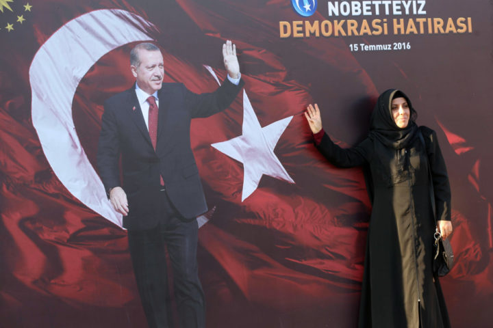 2016-08-02 17:36:21 A woman poses next to a picture of Turkish President Recep Tayyip Erdogan set up on a billboard at the Kizilay Square in Ankara during a protest against the failed military coup, on August 2, 2016. Erdogan said on August 2, 2016 last month's attempted coup was a scenario drawn up from outside Turkey, in an allusion to possible foreign involvement in the plot. / AFP PHOTO / ADEM ALTAN