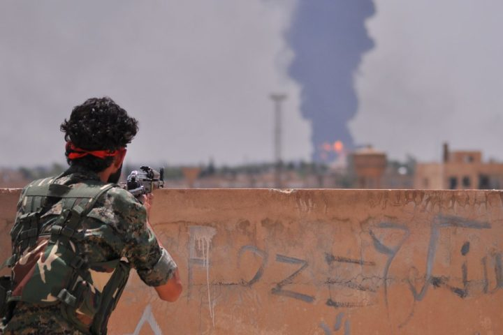 2015-06-28 11:22:05 A fighter from the Kurdish People Protection Unit (YPG) watches smoke billowing in the northeastern Syrian city of Hasakeh on June 28, 2015. IS seized two neighbourhoods in southern Hasakeh last week in a new attempt to seize the provincial capital, causing tens of thousands of people to flee, according to the United Nations. AFP PHOTO / DELIL SOULEIMAN