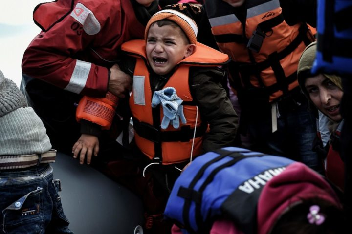 "2016-02-23 06:05:00 TOPSHOT - A child reacts as refugees and migrants disembark a rubber boat upon arrival at the northern island of Lesbos after crossing the Aegean sea from Turkey, in Mytilene, on February 23, 2016. Athens has expressed its ""displeasure"" to the EU over tougher border controls by Balkan countries that have left thousands of migrants stranded in Greece, Prime Minister Alexis Tsipras' office said on February 23. / AFP / ARIS MESSINIS"