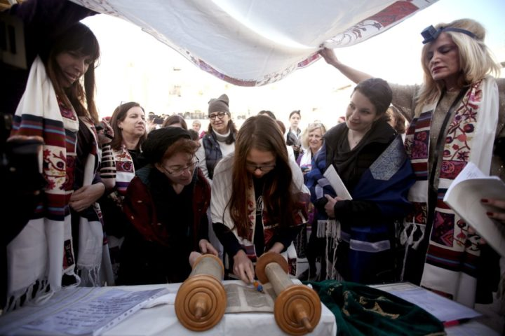 "2016-03-11 03:45:33 A young member of the liberal Jewish religious group Women of the Wall wears a ""Tallit"", a traditional Jewish prayer shawls for men, as she reads from a Tora scroll at the Western Wall in Jerusalem's Old City, on March 11, 2016, marking Rosh Hodesh Adar B (first day of the Jewish month). / AFP PHOTO / GALI TIBBON"