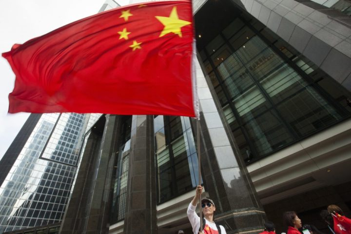 2016-05-18 09:24:53 epa05313398 A pro-China protester waves a large Chinese flag during a demontration in Wan Chai, near the venue of the 'One Belt, One Road' Summit where China's National People's Congress Standing Committee Chairman Zhang Dejiang gave a keynote speech to Hong Kong's ruling elite in Hong Kong, China, 18 May 2016. Zhang Dejiang is the third most powerful member of China's ruling politburo and is the most senior Chinese official to visit Hong Kong since the large scale Occupy Central / Umbrella Movement protests hit the city in 2014. EPA/ALEX HOFFORD