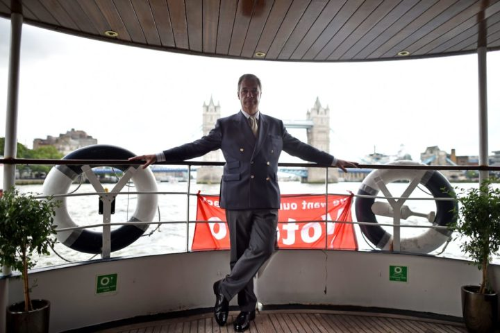 UK Independence party leader Nigel Farage poses in a passenger boat as he accompanies a Brexit flotiall of fishing boats on the river Thames in London on June 15, 2016. A Brexit flotilla of fishing boats sailed up the River Thames into London today with foghorns sounding, in a protest against EU fishing quotas by the campaign for Britain to leave the European Union. / AFP PHOTO / BEN STANSALL