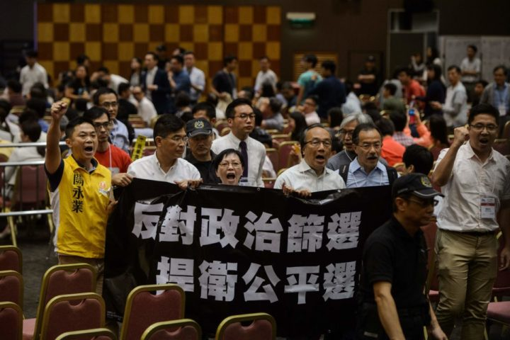 "2016-08-02 19:32:06 Pro-democracy supporters shout slogans and hold a banner which translates as ""Oppose Political Vetting, Defend Fair Elections"" as they walk out during the 2016 Legislative Council Election Briefing for Candidates in Hong Kong on August 2, 2016. A high-profile Hong Kong pro-independence leader said August 2 he had been barred from standing in upcoming parliamentary elections -- the latest candidate backing separation from mainland China to be disqualified. The apparent ban for Edward Leung, of the Hong Kong Indigenous party, from the September vote came despite him signing a controversial new form declaring Hong Kong is an ""inalienable"" part of China. / AFP PHOTO / Anthony WALLACE"