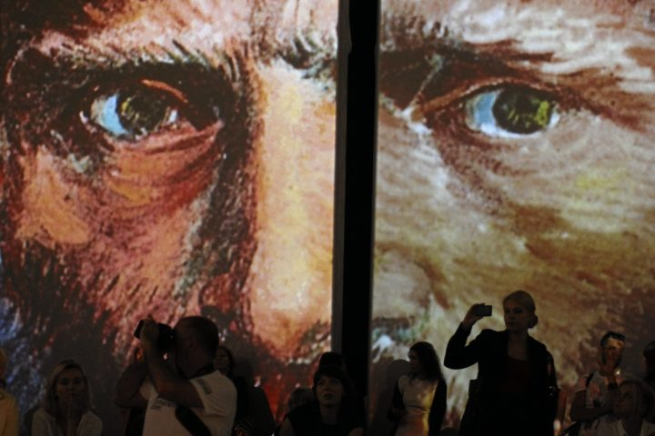 2016-08-18 00:00:00 epa05495759 Visitors look at giant illuminated panels depicting some works of Dutch painter Vincent Van Gogh (1853-1890) at the multimedia exhibition 'Van Gogh Alive - The Experience' in Krakow, Poland, 18 August 2016. The multimedia exhibition using the SENSORY4 technology shows more than 3,000 masterpieces of Vincent Van Gogh. The works displayed on walls, columns, ceiling and even on the floor in the form of large, pulsating color images, tell the story about the life and work of Van Gogh. The exhibition will be open to the public on 20 August. EPA/STANISLAW ROZPEDZIK POLAND OUT