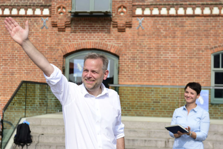 2016-08-27 13:08:46 Leif-Erik Holm (L), top candidate for regional elections of the Alternative for Germany (AfD) party, greets his supporters as he is applauded by AfD party chairwoman Frauke Petry during an election campaign event in Wismar, northeastern Germany, on August 27, 2016. On September 4, 2016, regional elections will be held on German Chancellor Angela Merkel's home turf of Mecklenburg-Western Pomerania, where her Christian Democratic Union (CDU) party is trailing in the polls. / AFP PHOTO / TOBIAS SCHWARZ