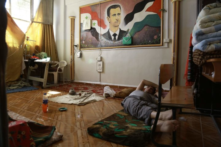 "2016-09-16 11:27:19 A man suffering from a mental disorder lies under a portrait of the Syrian president at a school used as shelter by displaced families fleeing the Islamic State (IS) group, on September 16, 2016, in the Kurdish-majority northeastern city of Qamishli. Qamishli is under the shared control of the Syrian regime and Kurdish authorities, who have declared zones of ""autonomous administration"" across parts of north and northeast Syria. / AFP PHOTO / DELIL SOULEIMAN"