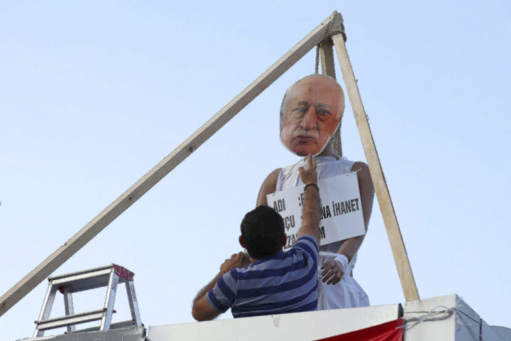 A man attaches a mask with the image of United States extradite Fethullah Gulen, who is accused of being behind the violent July 15 coup, by a makeshift gallows at the Kizilay square in Ankara, Turkey, Friday, July 29, 2016. The government crackdown in the coup's aftermath has strained Turkey's ties with key allies including the United States. (AP Photo/Ali Unal)
