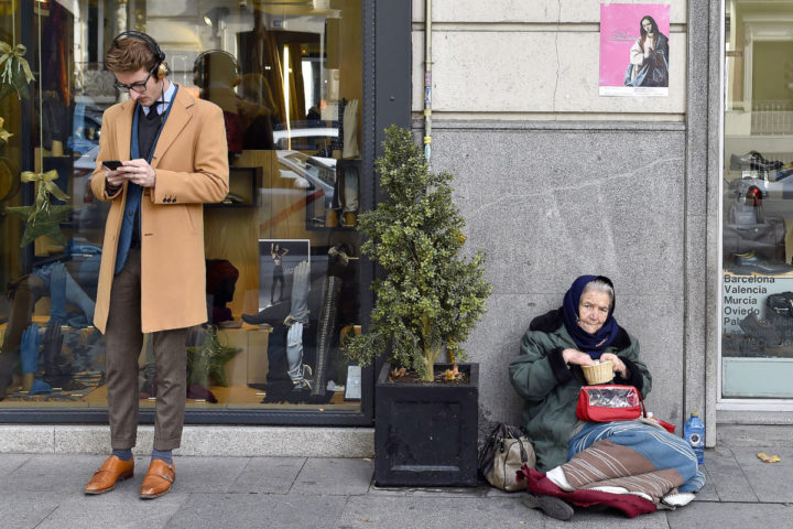 "2015-12-15 12:45:50 A man consults a mobile phone beside a woman begging on the pavement outside a clothes store in Salamanca an upscale neighbourhood of Madrid on December 15, 2015. The number of millionaires in Spain -- defined as having a fortune of over a million US dollars excluding their main residence and consumer goods -- rose by 40 percent to 178,000 last year from 2008 when the crisis started, according to consulting firm Capgemini. At the same time the number of people living with ""severe material deprivation"" in the country has doubled since 2007 to just over three million last year, according to a study by anti-poverty agency Oxfam.  AFP PHOTO/ GERARD JULIEN / AFP PHOTO / GERARD JULIEN"