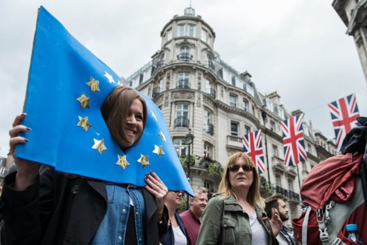 2016-07-02 12:43:32 A woman with her head, through a placard of the flag of Europe is pictured in the crowd as thousands of protesters take part in a March for Europe, through the centre of London on July 2, 2016, to protest against Britain's vote to leave the EU, which has plunged the government into political turmoil and left the country deeply polarised. Protesters from a variety of movements march from Park Lane to Parliament Square to show solidarity with those looking to create a more positive, inclusive kinder Britain in Europe. / AFP PHOTO / CHRIS J RATCLIFFE