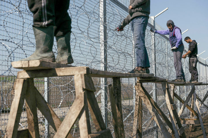 2016-03-18 09:35:42 Workers attach barbed wire to a border fence to prevent illegal crossings by migrants at the Bulgarian-Turkish border near the Bulgarian village of Shtit on March 18, 2016. EU leaders approved a controversial deal with Turkey to curb the huge flow of asylum seekers to Europe, with all migrants arriving in Greece from March 13, 2016 to be sent back. / AFP PHOTO / DIMITAR DILKOFF