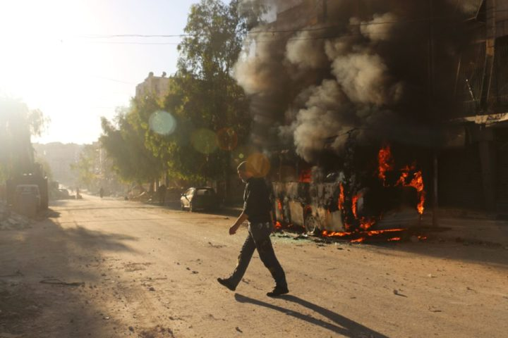 2016-09-25 14:24:38 A Syrian man walks past a bus set ablaze following a reported air strike in the rebel-held Salaheddin district of Aleppo on September 25, 2016. The UN Security Council met for urgent talks as Syrian and Russian warplanes pounded rebel-held east Aleppo in the worst surge of bombing to hit the devastated city in years. Britain, France and the United States called the emergency meeting to turn up pressure on Russia and press demands that it rein in its ally Syria to halt the intense bombing campaign on Aleppo. / AFP PHOTO / AMEER ALHALBI