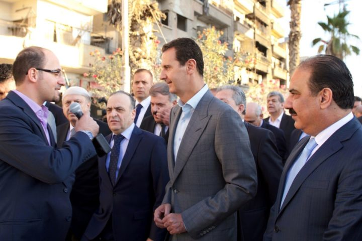 """A handout picture released by the official Syrian Arab News Agency (SANA) on September 12, 2016, shows Syrian President Bashar al-Assad (C) speaking with the press as he walks in the street alongside officials after performing the morning Eid al-Adha prayer at a mosque in a government-controlled area of Daraya. / AFP PHOTO / SANA / HO / == RESTRICTED TO EDITORIAL USE - MANDATORY CREDIT """"AFP PHOTO / HO / SANA"""" - NO MARKETING NO ADVERTISING CAMPAIGNS - DISTRIBUTED AS A SERVICE TO CLIENTS =="""