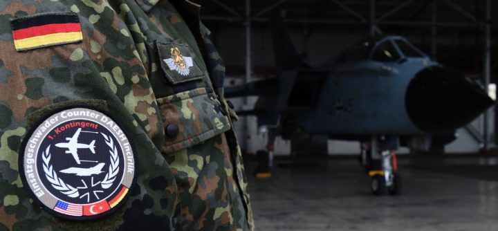 2016-01-21 10:15:01 A soldier of the German Armed Forces Bundeswehr wears a badge of the combat wing (Einsatzgeschwader) Counter DAESH Incirlik next to a German Tornado jet in a hangar before a statement of the German and Turkish defence ministers at the air base in Incirlik, Turkey, on January 21, 2016. / AFP / POOL / TOBIAS SCHWARZ