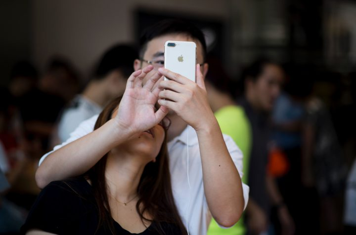 2016-09-16 11:24:59 TOPSHOT - A Chinese couple tests the new iPhone 7 during the opening sale launch at an Apple store in Shanghai on September 16, 2016. With new iPhones hitting the markets on September 16, Apple is seeking to regain momentum and set new trends for the smartphone industry and tech sector. / AFP PHOTO / JOHANNES EISELE