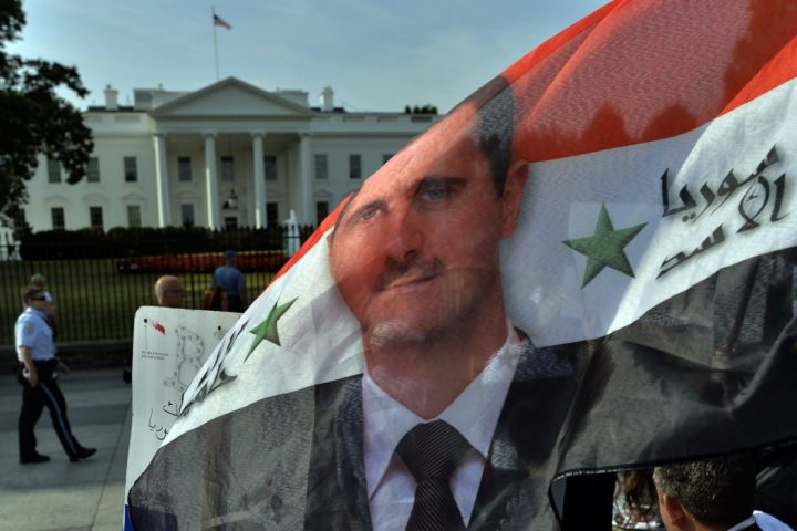 2013-09-09 09:49:46 Supporters of Syrian President Bashar Al-Assad wave a Syrian flag with Assad's flag on it during a demonstration in front of the White House in Washington, DC, on September 9, 2013 urging US not to attack Syria. US Presidents Barack Obama and Bashar Al-Assad will go head-to-head in dueling US television interviews Monday, as a crucial week dawns for the US leader's push for air attacks on Syria. Assad denied that he used chemical weapons on civilians, as Obama makes a long-odds push to reverse his nation's mood and win support for punishing the Damascus regime for flouting taboos on the use of such arms. AFP Photo/Jewel Samad