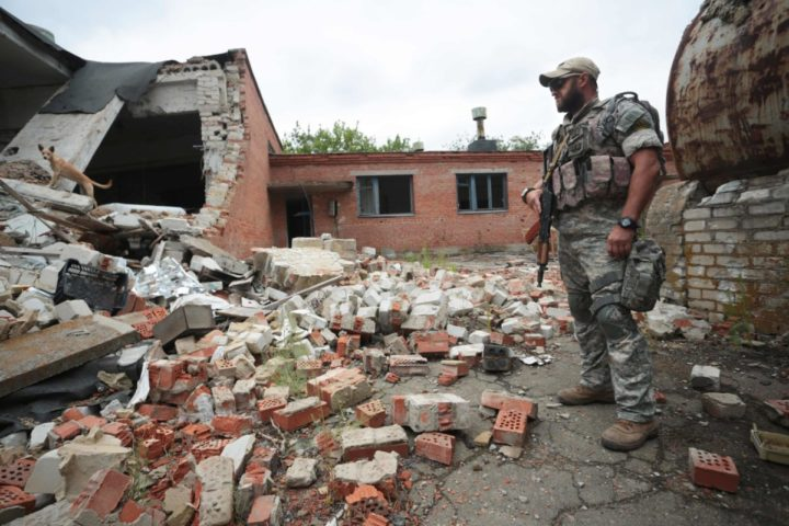 "2016-08-14 09:10:47 TO GO WITH AFP STORY BY YULIA SILINA A Ukrainian paratrooper, with the nom-de-guerre Boroda (Beard), and member of an air assault battalion defending the small town of Shyrokyne, in Donetsk region, walks among the ruins of building destroyed by pro-Russian separatists shelling on August 14, 2016. Ukrainian paratrooper Boroda says pro-Russian rebels have recently ramped up their shelling of one key village -- a move he links to Moscow's claim of a Kiev plot against annexed Crimea. Boroda, or ""the Beard"", is the nom de guerre of a member of an air assault battalion defending the once quiet coastal resort village of Shyrokyne that has turned into one of the bloodiest battlefields of the 27-month separatist revolt. / AFP PHOTO / ALEKSEY FILIPPOV"