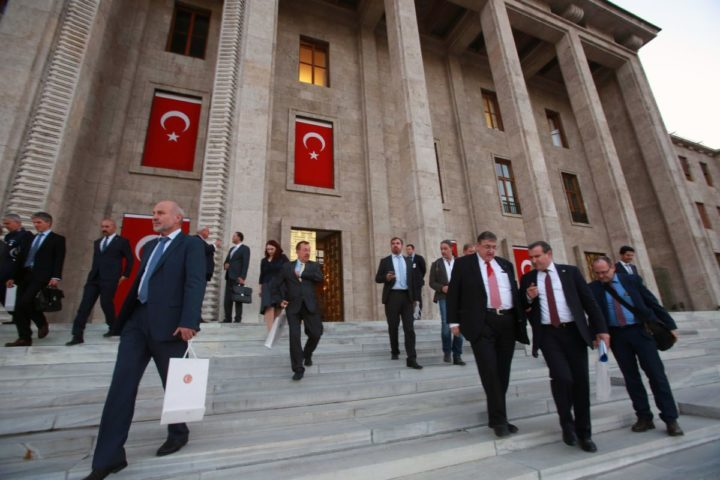 2016-10-04 21:03:43 Karl Lamers (3R) Deputy Chairman of the German Parliament's Defence Committee, accompanied by Turkish MPs and German parliamentarians, leaves after visiting Turkish Parliament which was partly damaged during the July 15 coup attempt in Ankara, on October 4, 2016. / AFP PHOTO / ADEM ALTAN