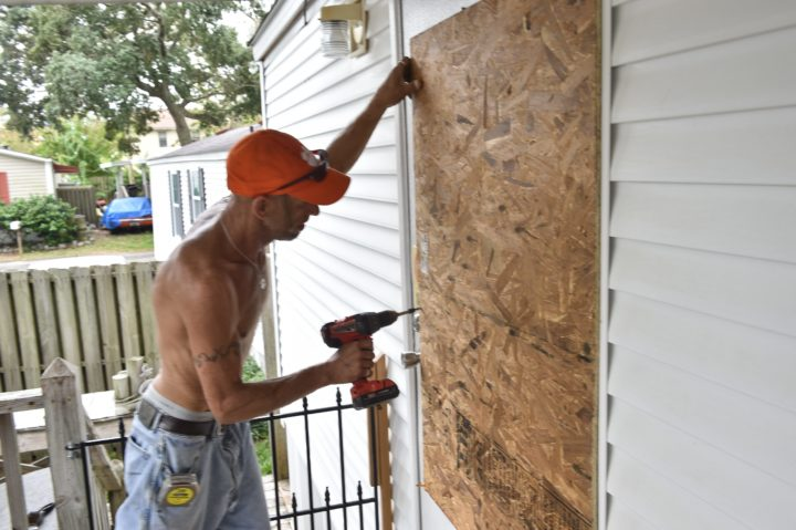 2016-10-06 14:58:43 A worker boards up the door of a house in in Myrtle Beach, South Carolina, on October 6, 2016 as Hurricane Matthew makes its way towards the United States. Some three million people on the US southeast coast faced an urgent evacuation order Thursday as monstrous Hurricane Matthew -- now blamed for more than 100 deaths in Haiti alone -- bore down for a direct hit on Florida. / AFP PHOTO / NICHOLAS KAMM