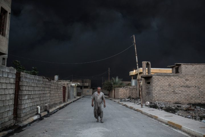 2016-10-19 14:10:19 TOPSHOT - An Iraqi man walks on a street covered with smoke after a fire from oil was set ablaze in the Qayyarah area, some 60 kilometres (35 miles) south of Mosul, on October 19, 2016, during an operation by Iraqi forces against Islamic State (IS) group jihadists to retake the main hub city. In the biggest Iraqi military operation in years, forces have retaken dozens of villages, mostly south and east of Mosul, and are planning multiple assaults for October 20. / AFP PHOTO / YASIN AKGUL