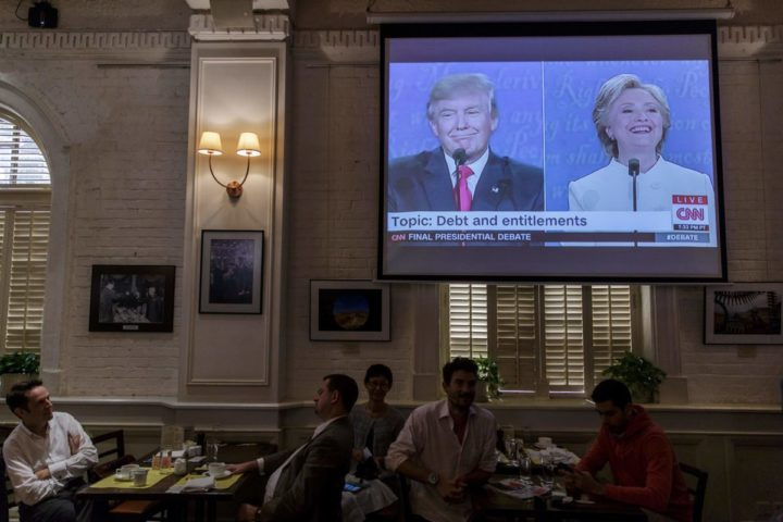 2016-10-20 11:43:44 People watch a live screening of the third and final presidential debate between Republican nominee Donald Trump (L on screen) and Democratic nominee Hillary Clinton (R on screen), in Hong Kong on October 20, 2016. / AFP PHOTO / Anthony WALLACE