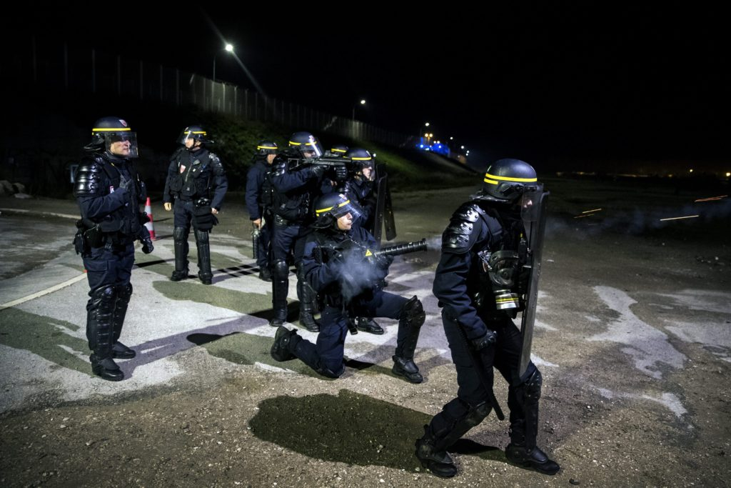 2016-10-22 20:27:43 epa05598412 A French riot police officer shots tear gas at migrants as they attack the fence next to the makeshift camp 'the Jungle' in Calais, France, 22 October 2016. The camp gathering more than 7,000 migrants will be dismantled on 24 October, a process that shall take a week according tho the French authorities. EPA/ETIENNE LAURENT