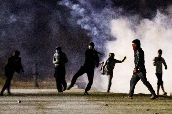 2016-10-22 20:27:43 epa05598414 Migrants clash with French riot Police as they attack the fence next to the makeshift camp 'the Jungle' in Calais, France, 22 October 2016. The camp gathering more than 7,000 migrants will be dismantled on 24 October, a process that shall take a week according tho the French authorities. EPA/ETIENNE LAURENT