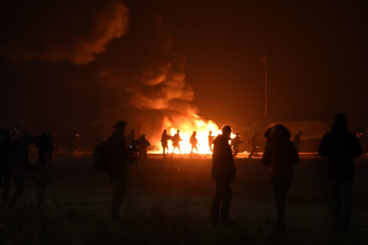 "2016-10-23 20:24:57 Migrants start a fire during clashes with French police at the ""Jungle"" migrant camp in Calais, northern France, on October 23, 2016 on the eve of the camp's planned evacuation. On the eve of the demolition of the Calais ""Jungle"" camp, French officials handed out flyers in several languages notifying migrants of the camp's imminent closure and urging them to abandon their dreams of reaching Britain. / AFP PHOTO / DENIS CHARLET"