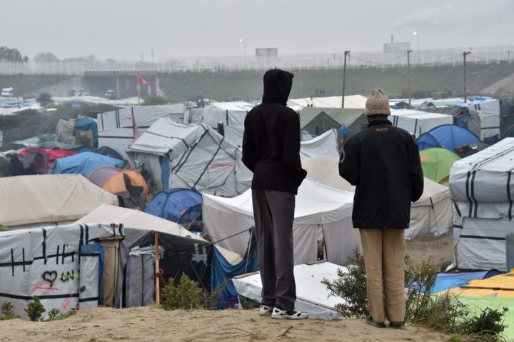 "2016-10-24 07:13:33 Migrant look on at the ""Jungle"" migrant camp in Calais, northern France, early on October 24, 2016, as a major three-day operation is planned to clear the camp of its estimated 6,000-8,000 occupants. French authorities are set to begin on October 24, 216 moving thousands of people out of the notorious Calais Jungle before demolishing the camp that has served as a launchpad for attempts to sneak into Britain. Migrants carrying suitcases and bundles of possessions started queueing up in the early morning darkness at the official meeting points for transportation to reception centres across France. A major three-day operation is planned to clear the sprawling shanty town near Calais port -- a symbol of Europe's failure to resolve its migrant crisis -- of its estimated 6,000-8,000 occupants. / AFP PHOTO / PHILIPPE HUGUEN"