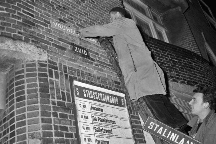 """Een werknemer van de Amsterdamse Dienst van Publieke Werken vervangt in Amsterdam-Zuid de straatnaamplaten met """"Stalinlaan"""" door - voorlopig houten- bordjes met """"Vrijheidslaan"""", na een besluit van de Amsterdamse gemeenteraad"""