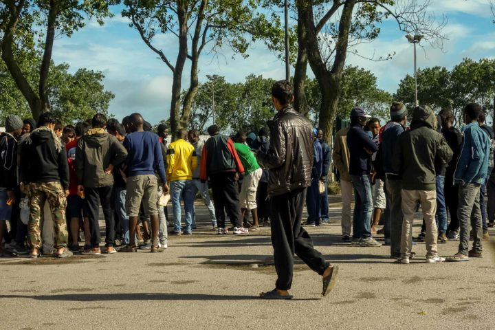 """2016-08-22 09:46:21 Migrants gather and talk outside the Jules-Ferry aid centre on August 22, 2016 in Calais, next to the so-called """"Jungle"""" migrant camp. / AFP PHOTO / PHILIPPE HUGUEN"""