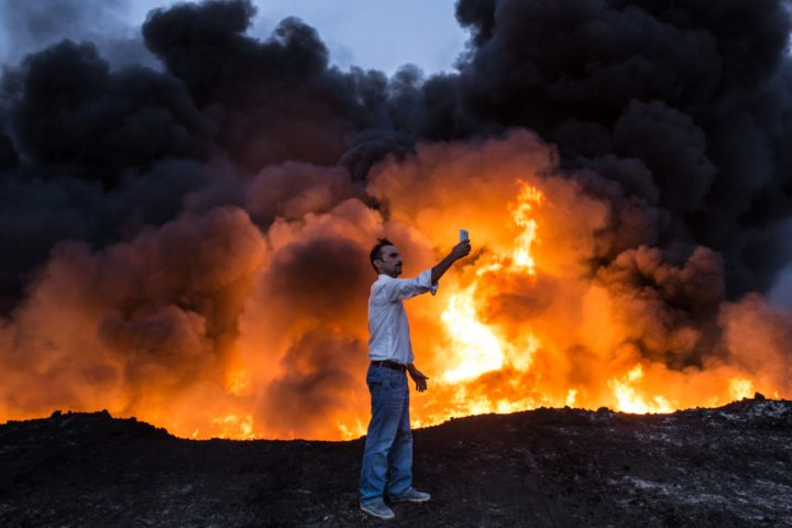 TOPSHOT - A man takes a selfie in front of a fire from oil that has been set ablaze in the Qayyarah area, some 60 kilometres (35 miles) south of Mosul, on October 19, 2016, during an operation by Iraqi forces against Islamic State (IS) group jihadists to retake the main hub city. In the biggest Iraqi military operation in years, forces have retaken dozens of villages, mostly south and east of Mosul, and are planning multiple assaults for October 20. / AFP PHOTO / YASIN AKGUL