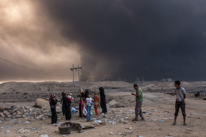 2016-10-19 12:10:08 Iraqi villagers gather on a road as smoke rises from the Qayyarah area, some 60 kilometres (35 miles) south of Mosul, on October 19, 2016, during an operation by Iraqi forces against Islamic State (IS) group jihadists to retake the main hub city. In the biggest Iraqi military operation in years, forces have retaken dozens of villages, mostly south and east of Mosul, and are planning multiple assaults for October 20. / AFP PHOTO / YASIN AKGUL