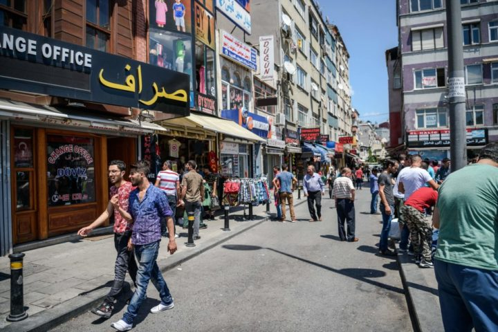 2016-07-04 13:01:48 Syrian and Turkish people walk in a street next to shops with Arabic letters on July 4 ,2016 in Fatih neighbourhood in Istanbul. Receptionist, waiter, hairdresser, pastry-seller : these are the jobs of the young Syrians who abandoned their dreams in Damascus to start from scratch in Istanbul. In Fatih, a densely-packed neighbourhood that serves as a hub for Arabs living in Turkey's biggest city, the signs of home are everywhere. / AFP PHOTO / OZAN KOSE