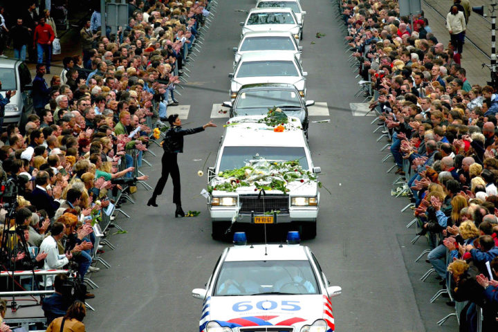 NLD-20020507-ROTTERDAM: Een vrouw gooit bloemen op de auto met het stoffelijk overschot van Pim Fortuyn. De begrafenisstoet is op weg naar de kathedraal in Rotterdam waar de uitvaartdienst wordt gehouden. Fortuyn wordt later begraven op de begraafplaats Westerveld in Driehuisen. ANP FOTO/ROBIN UTRECHT