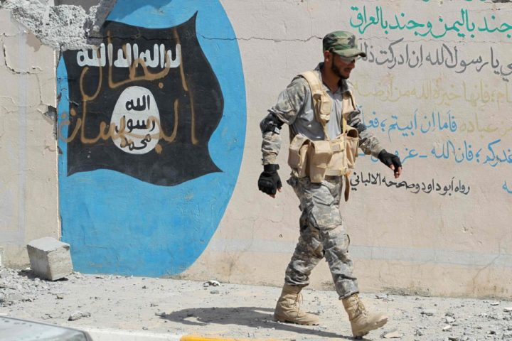 2016-09-23 12:00:56 A member of the Iraqi government forces walk past a Islamist flag covered in grafitti in the town of Sharqat, around 80 kilometres (50 miles) south of the city of Mosul, on September 23, 2016, the day after they recaptured the northern city from the Islamic State (IS) group. Security forces began the operation on September 20, 2016 to oust the Islamic State group from Sharqat, a town near supply lines needed for the battle to retake second city Mosul from the jihadists. / AFP PHOTO / AHMAD AL-RUBAYE