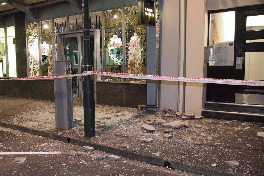 2016-11-14 00:00:00 Debris from buildings are seen on a sidewalk past a cordon line in Wellington early on November 14, 2016 following an earthquake centred some 90 kilometres (57 miles) north of New Zealand's South Island city of Christchurch. A powerful 7.8 magnitude earthquake rocked New Zealand early November 14, the US Geological Survey said, prompting a tsunami warning and knocking out power and phone services in many parts of the country. / AFP PHOTO / Marty Melville