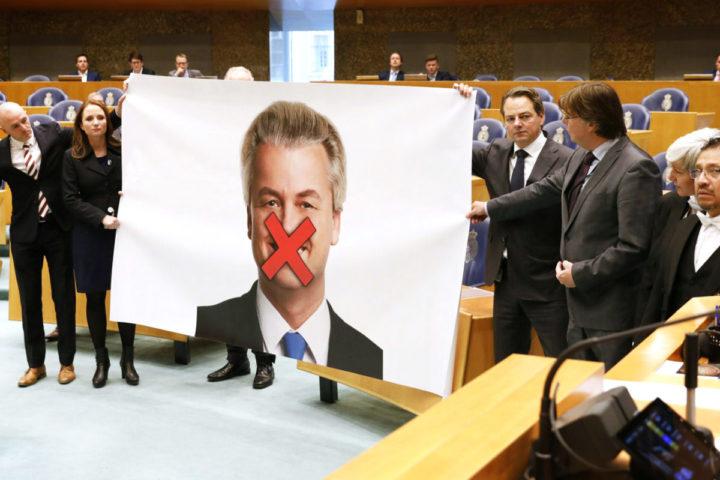 2016-11-17 12:34:25 DEN HAAG - PVV-fractieleden protesteren in de Tweede Kamer tegen de strafeis van hun leider Geert Wilders, doormiddel van een grote poster van Wilders met een rood kruis over zijn mond. ANP BART MAAT