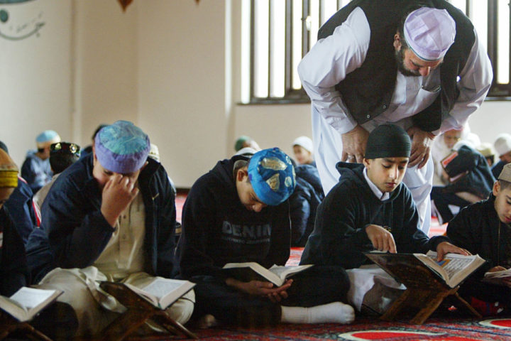 2004-04-15 14:46:00 Haji Muhammad Sulaiman (C) helps a class of young boys learn The Koran at The Central Mosque in Luton 15 April 2004. Sulaiman is President of The Islamic Cultural Society in the area. Luton's population has a high concentration of Muslims and received unwanted media attention after several men were arrested in connection with terrorist offences earlier in the year. AFP PHOTO Adrian DENNIS