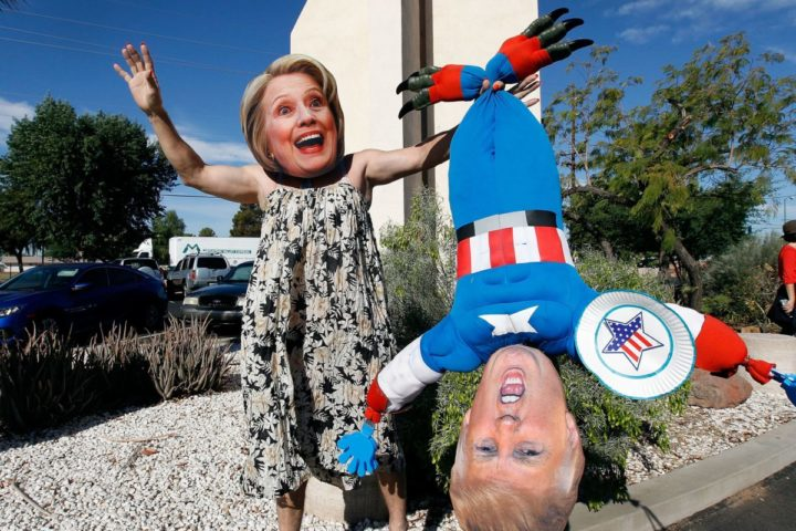 2016-11-08 00:00:00 PHOENIX, AZ - NOVEMBER 08: Hillary Clinton supporter Jorge Mendez of Glendale, Arizona wears a dress and Hillary Clinton mask while holding a makeshift doll of Donald Trump after voting on November 8, 2016 in Phoenix, United States. Americans across the nation are picking their choice for the next president of the United States. Ralph Freso/Getty Images/AFP == FOR NEWSPAPERS, INTERNET, TELCOS & TELEVISION USE ONLY ==