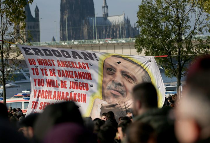 2016-11-12 00:00:00 epa05628230 Kurds and Alevi hold a banner with Turkish President Recep Tayyip Erdogan picture reading 'You will be judged' protest against the Turkish President in Cologne, Germany, 12 November 2016. Around 10,000 Alevi and Kurds gathered for a demonstration against the policies of Turkish President Erdogan. EPA/OLIVER BERG