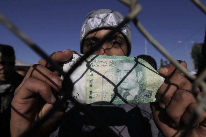 2015-12-13 10:24:19 epa05067500 A migrant from Morocco holds a banknote of his country as he participates in a protest asking for open borders, in the premises of a former Olympic Stadium, in Athens, Greece, 13 December 2015. The migrants, who are temporary housed in the stadium of TAE-KWO-NDO, have been removed with buses earlier this week by the Greek Police from Idomeni, north Greece, as they have been rejected from FYR of Macedonia as economic migrants. Former Yogoslavic Republic of Macedonia allows the entrance only to refugees from Syria, Iraq and Afghanistan, rejecting all others. EPA/ORESTIS PANAGIOTOU