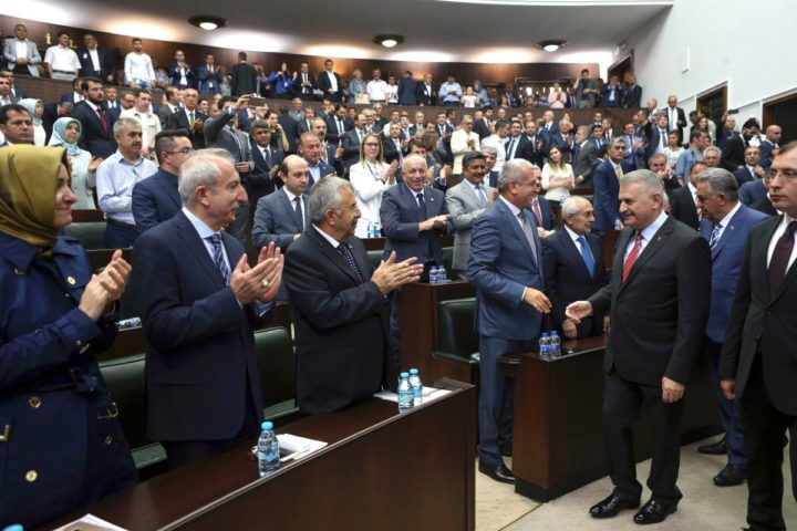 2016-08-16 12:29:48 Turkish Prime Minister and the leader of Turkey's ruling party, the Justice and Development Party (AK Party) Binali Yildirim (2nd R) salutes the assembly after his statement during an AK Party's group meeting at the Grand National Assembly of Turkey (TBMM) in Ankara, on August 16, 2016. / AFP PHOTO / ADEM ALTAN