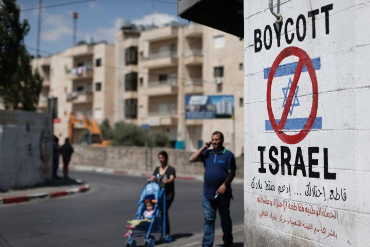 2015-06-05 07:44:11 (FILES) This file photo taken on June 05, 2015 shows Palestinians walking past a sign painted on a wall in the West Bank biblical town of Bethlehem on June 5, 2015, calling to boycott Israeli products coming from Jewish settlements. The international BDS (boycott, divestment and sanctions) campaign, that pushes for a ban on Israeli products, aims to exert political and economic pressure over Israel's occupation of the Palestinian territories in a bid to repeat the success of the campaign which ended apartheid in South Africa. / AFP PHOTO / THOMAS COEX / TO GO WITH AFP STORY BY JOE DYKE