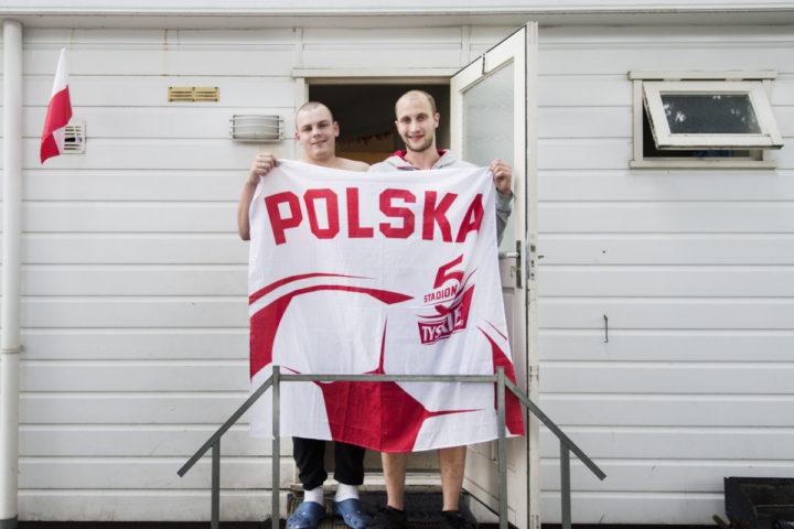 2016-06-28 20:42:54 OSS - Poolse arbeidsmigranten tonen een vlag van hun land bij hun woning op een recreatiepark in Oss. Arbeiders uit Polen worden in Nederland nog altijd uitgebuit. Ze maken vaak lange dagen, worden verplicht onbetaald over te werken en kampen met seksuele intimidatie en bedreigingen. Dat concluderen onderzoeksstichting SOMO en stichting FairWork op basis van gesprekken met meer dan honderd Poolse arbeiders. ANP PIROSCHKA VAN DE WOUW