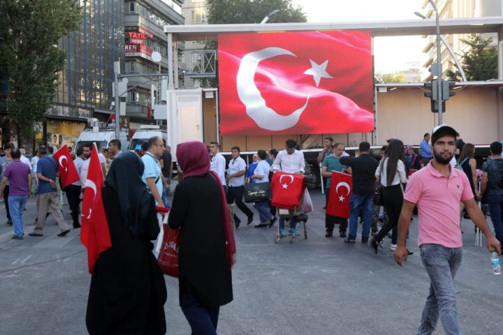 2016-07-25 20:00:05 Pro-Erdogan supporters gather next to a Turkish flag during a rally against the military coup at Kizilay Square in Ankara, on July 25, 2016. journalists in a new phase of the controversial legal crackdown after the failed coup against President Recep Tayyip Erdogan, sparking fresh alarm over the scope of the detentions. / AFP PHOTO / ADEM ALTAN