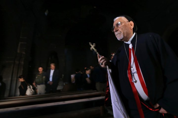 2016-10-30 00:00:00 Archbishop Yohanna Petros Mouche of Mosul prays at the St. George Syriac Catholic Church in the Christian Iraqi town of Bartella, about 15 kilometres (10 miles) east of Mosul on October 30, 2016, after Iraqi forces recaptured it from Islamic State (IS) group jihadists. Iraqi forces are fighting their way toward Mosul to retake it from IS in an operation that is now in its second week, and some Christian villages have already been retaken. / AFP PHOTO / SAFIN HAMED